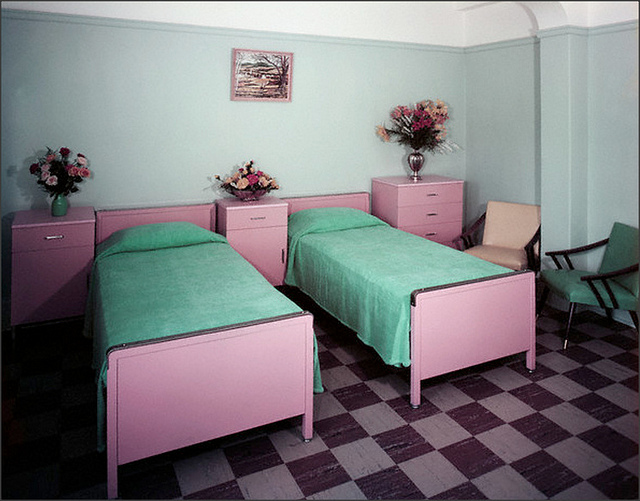 Pink bedside tables and pink beds with green bedding and a check pattern flooring