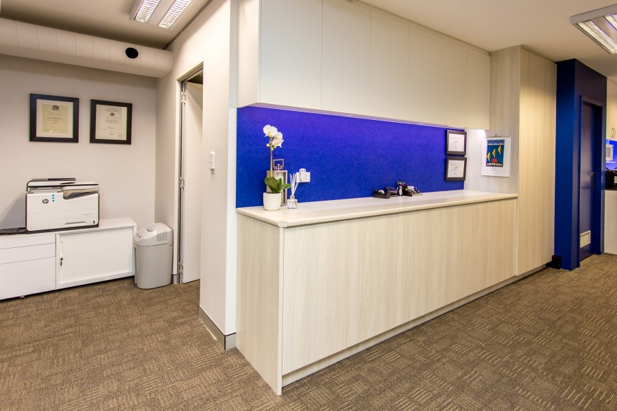 Custom white joinery with blue splashbacks in offices of Brain Partners