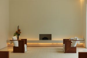 minimalist home living psace with 2 occasional chairs and a fireplace