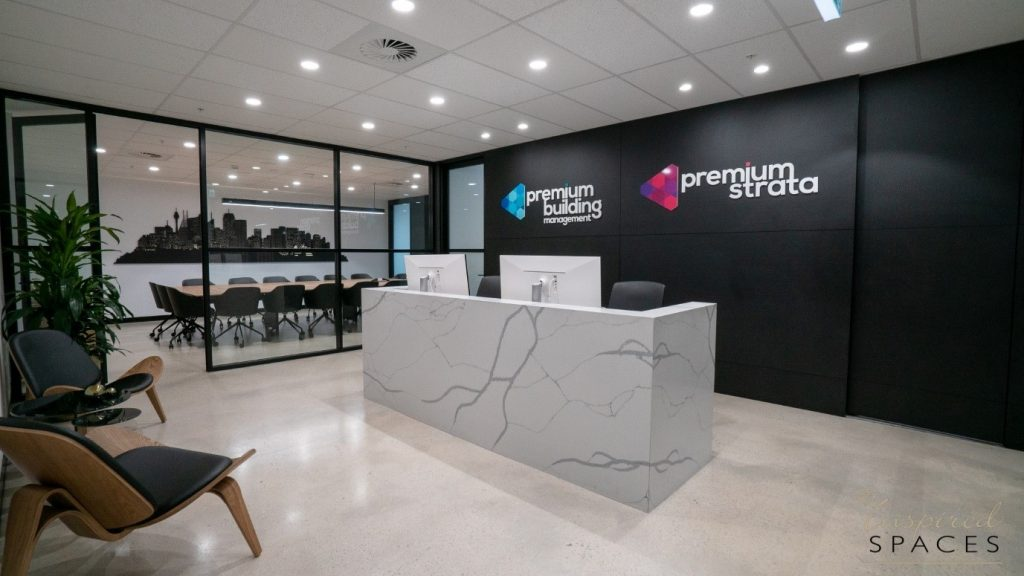 Beautful commercial reception area with black feature wall and carara marble desk