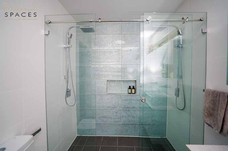 The double shower in this ensuite contains rain shower heads and a practical recess for his and her shampoos