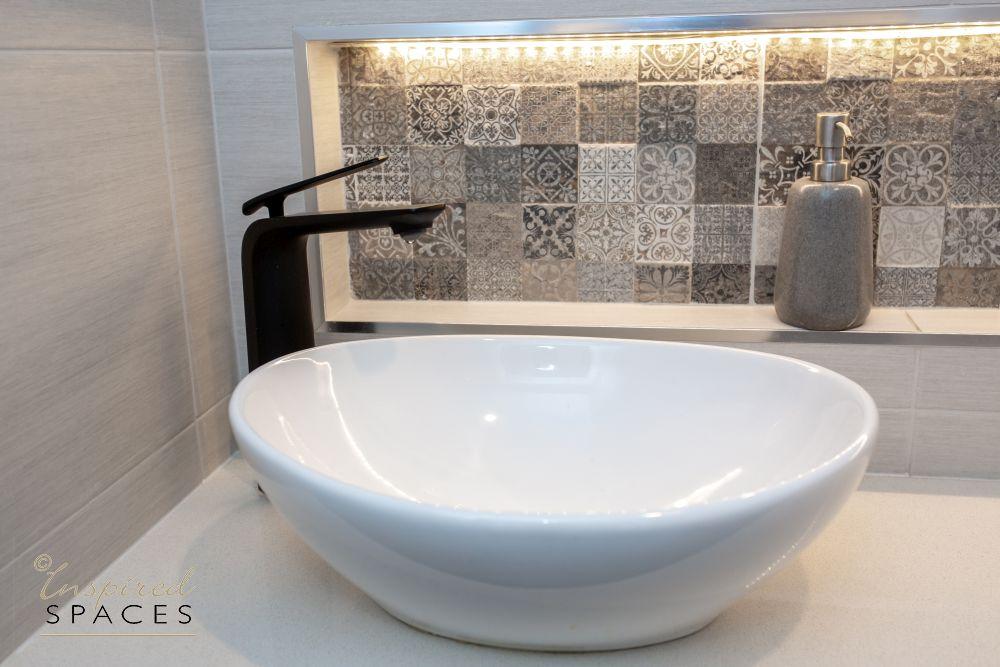 white basin and black tap in bathroom