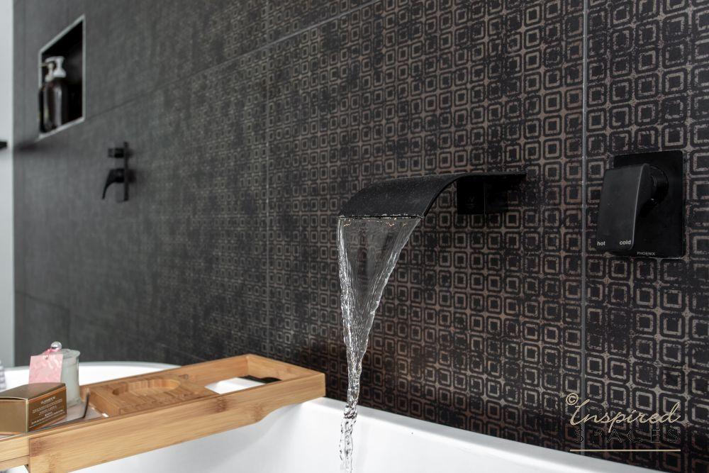 black flat water spout over bath