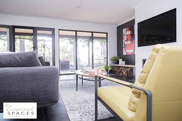 Living area with a tv, a yellow occasional chair and charcoal sofa