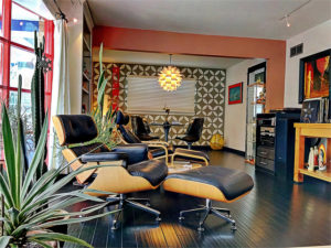 Bold prints, pops of colour and the iconic Eames chair give this space its mid-century modern look