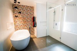 Main bathroom with Andy Warhol inspired tiles at the rear wall and pendant lights over the freestanding bath tub