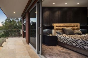 Master suite with customised furniture, fabrics and timber wall cladding to represent the clients' preferences