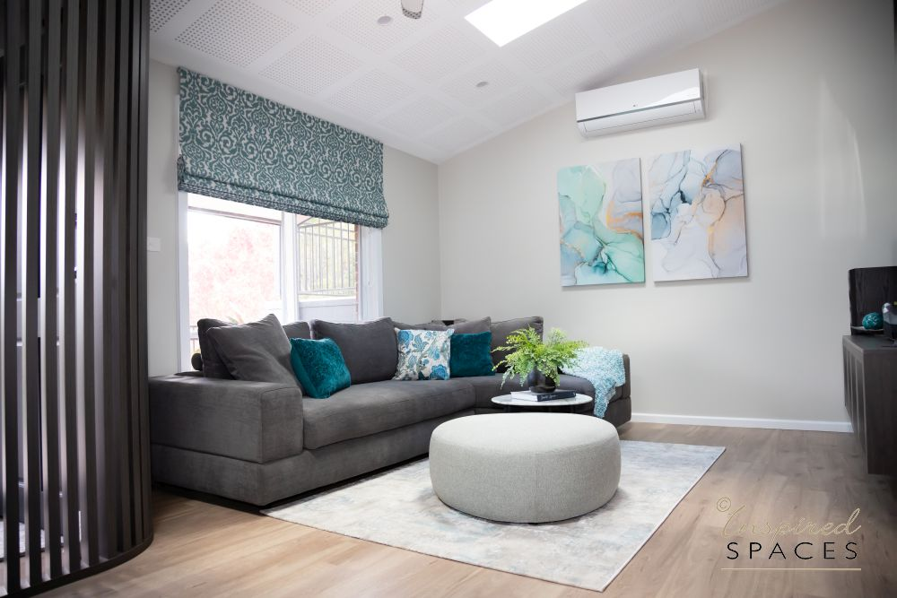 Grey sofa with turquoise cushions and roman blind