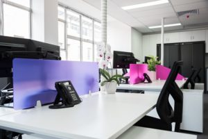White office desks with magenta and purple screens between gives the office space pops of colour