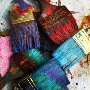 A collection of paint brushes covered in different coloured paints