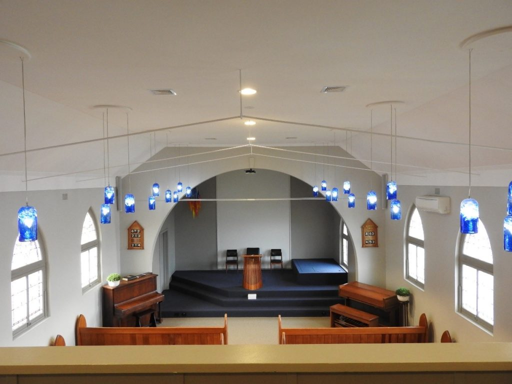 chapel after photo with navy carpet, grey walls and blue glass lighting