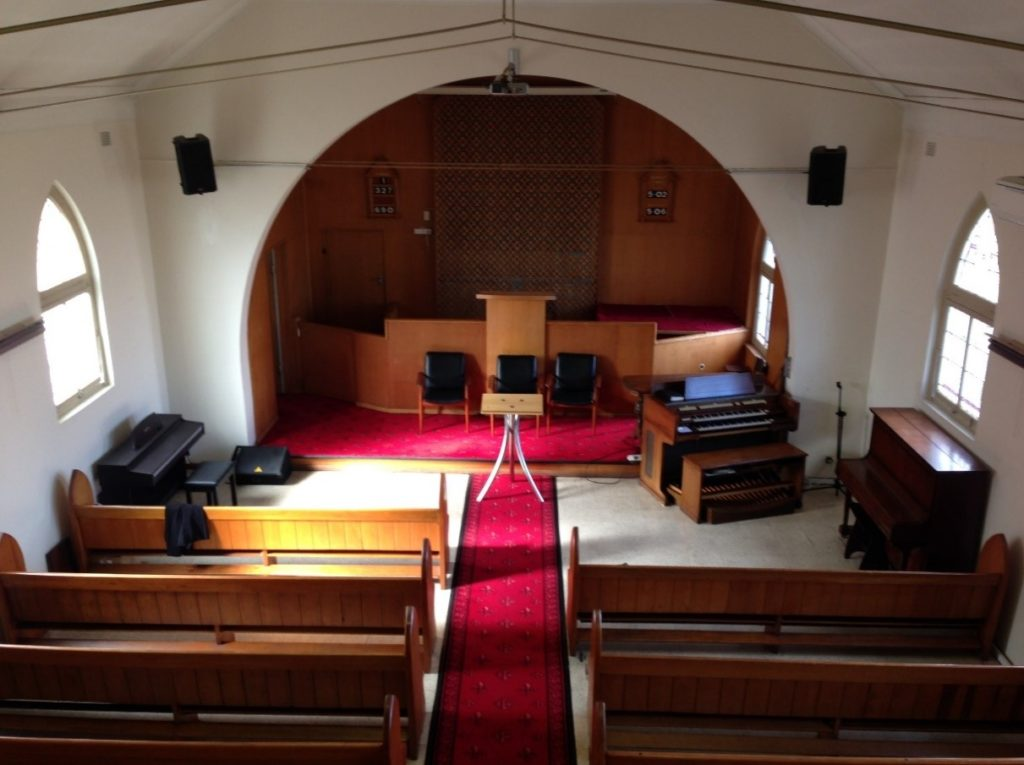 Chapel before image withwhite walls, red carpet and runner