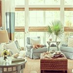 coastal living space with blue linen chairs and rattan coffee table