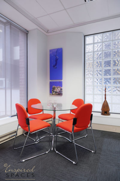 glass meeting table with orange chairs