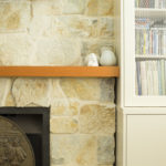 Sandstone fireplace with timber mantle and white built-in book shelf