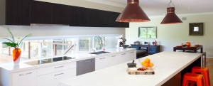Modern kitchen which cleverly utilises a long outside window as an interesting bench top 'splash back'