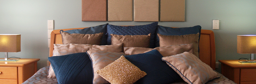 Artwork hung above a queen bed with lots of scatter cushions in navy and beige