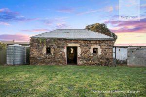 A metal water rainwater tank sits beside a beautiful old stone farmhouse
