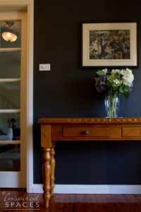Hallway with navy walls and white trim and a timber console with art