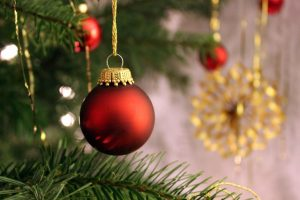 close up of red bauble hanging on christmas tree